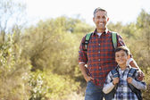 Father And Son Hiking In Countryside Wearing Backpacks — ストック写真