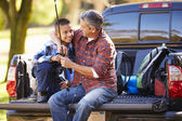 Father And Son Sitting In Pick Up Truck On Camping Holiday — Stock Photo