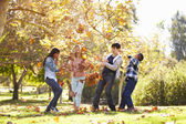 Four Children Throwing Autumn Leaves In The Air — Stock Photo
