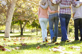 Retrovisor a família que anda através da floresta de outono — Foto Stock