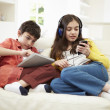 Children Playing With Digital Tablet And MP3 Player — Stock Photo #50473989
