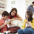 Family Playing With Digital Tablet And MP3 Player — Stock Photo #50474025
