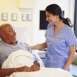 Nurse Talking To Senior Male Patient In Hospital Room — Stock Photo #50474123