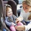 Mother Putting Baby Into Car Seat — Stok fotoğraf #50474481