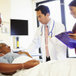 Medical Team Meeting With Senior Couple In Hospital Room — Stock Photo #50475041