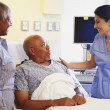 Nurse Talking To Senior Couple In Hospital Room — Foto Stock