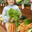 Young Girl Holding Bunch Of Carrots In Farm Shop — Stock Photo #50475197