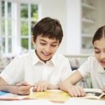Children Wearing School Uniform Doing Homework In Kitchen — Stock Photo #50475689