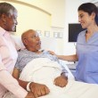 Nurse Talking To Senior Couple In Hospital Room — Stock Photo #50475919