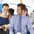 Businessman And Woman Looking At Mobile Phone On Bus — Stock Photo #50476031