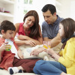 Family Playing With Digital Tablet And MP3 Player — Stock Photo #50476159