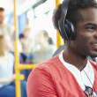 Man Wearing Headphones Listening To Music On Bus Journey — Stock Photo #50476503