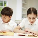 Children Wearing School Uniform Doing Homework In Kitchen — Stock Photo #50476683