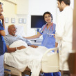 Medical Team Meeting With Senior Man In Hospital Room — Stock Photo #50476763