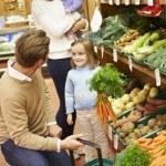 Family Choosing Fresh Vegetables In Farm Shop — Stock Photo #50477141