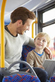Son Using Digital Tablet On Bus Journey With Father — Foto de Stock