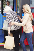 Woman Helping Senior Woman To Board Bus — Stockfoto