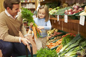 Father And Daughter Choosing Fresh Vegetables In Farm Shop — Foto Stock