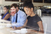 Businesswoman Writing Notes In Coffee Shop — Foto de Stock