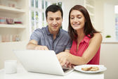 Couple Looking at Laptop Over Breakfast — Stock Photo