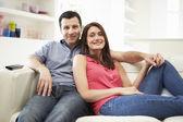 Hispanic Family Sitting On Sofa Watching TV Together — Stock Photo