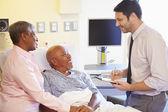 Medico parlando con coppia senior su ward — Foto Stock