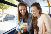 Two Young Women Reading Text Message On Bus — Stock Photo