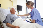 Nurse Talking To Senior Male Patient In Hospital Room — Stok fotoğraf