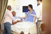 Medical Team Meeting With Senior Couple In Hospital Room — Stockfoto