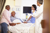 Medical Team Meeting With Senior Couple In Hospital Room — Photo