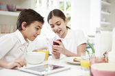 Schoolchildren With Digital Tablet And Mobile At Breakfast — Stock Photo