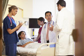 Medical Team Meeting Around Female Patient — Stockfoto