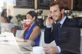 Businessman Using Mobile Phone And Laptop In Coffee Shop — Stock Photo