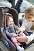 Mother Putting Baby Into Car Seat — Stock Photo