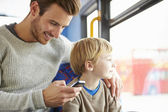 Father Using Mobile Phone On Bus Journey With Son — Stock Photo
