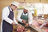 Butcher Teaching Apprentice How To Prepare Meat — Stockfoto