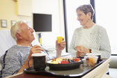Senior Couple In Hospital Room As Male Patient Has Lunch — Stock Photo