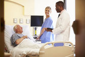 Medical Team Meeting With Senior Man In Hospital Room — Stockfoto