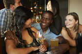 Group Of Friends Enjoying Drink At Bar Together — Stock Photo