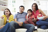 Hispanic Family Sitting On Sofa Watching TV Together — Stok fotoğraf
