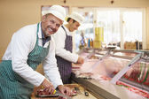 Two Butchers Preparing Meat In Shop — Stock Photo