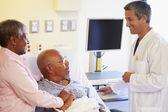 Läkare pratar med äldre par på ward — Stockfoto