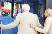 Woman Helping Senior Man To Board Bus — Стоковое фото