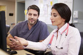 Female Doctor With Male Nurse Working At Nurses Station — Stock Photo