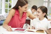Anne dijital tablet kullanarak ev ödevlerinde yardımcı kızı — Stok fotoğraf