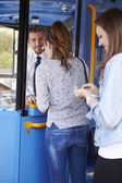 Two Young Women Boarding Bus And Buying Ticket — ストック写真