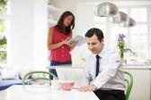 Casal usando dispositivos digitais na mesa de café da manhã — Fotografia Stock