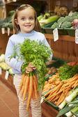 Young Girl Holding Bunch Of Carrots In Farm Shop — Foto de Stock