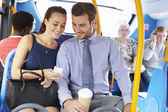 Businessman And Woman Looking At Mobile Phone On Bus — Stock Photo