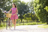 Attractive Woman Pushing Bike Along Country Lane — Stockfoto